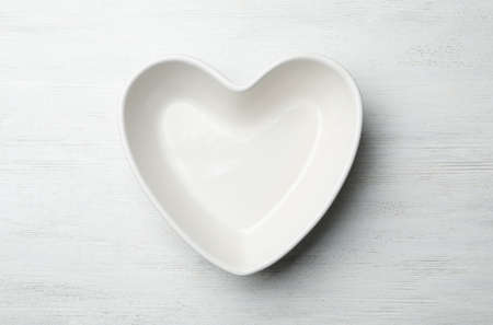 Heart shaped plate on white wooden background, top view