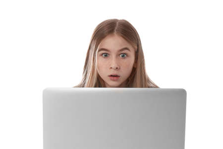 Shocked teenage girl with laptop on white background. Danger of internet Stock Photo - 124398384