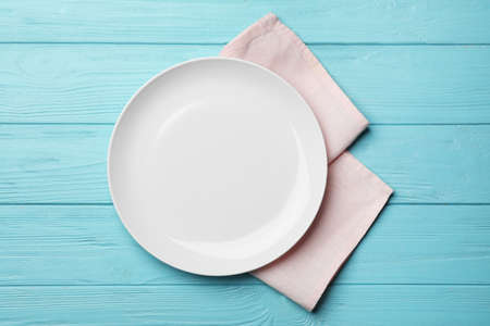 Stylish ceramic plate and napkin on color wooden background, flat lay