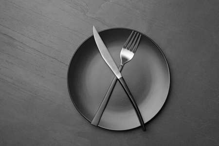 Stylish ceramic plate with crossed fork and knife on dark background, top view