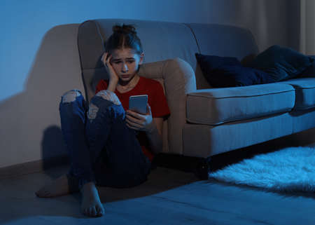 Emotional teenage girl with smartphone in dark room. Danger of internet Imagens - 124988329