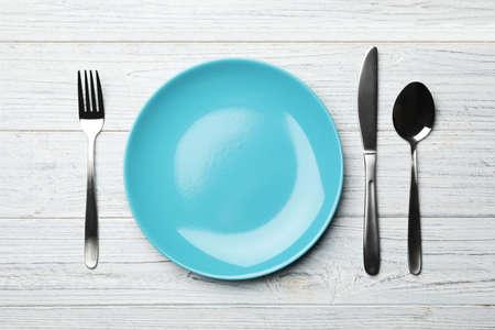 Stylowy talerz ceramiczny i sztućce na białym drewnianym tle, płaskie lay