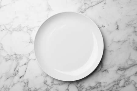 Stylish ceramic plate on marble background, top view