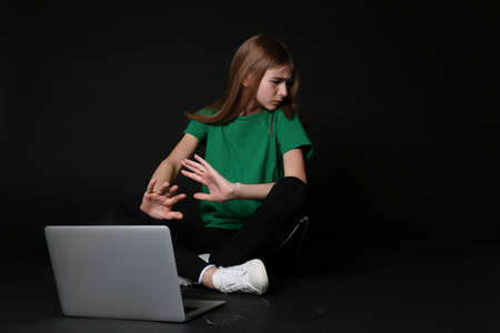 Scared teenage girl with laptop on black background. Danger of internet
