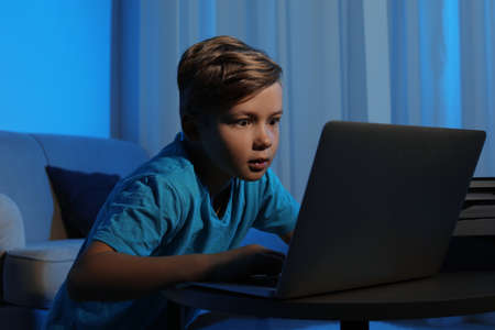 Shocked little child with laptop in dark room. Danger of internet