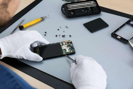 Tecnico che ripara smartphone rotto al tavolo, primo piano