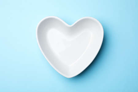Heart shaped plate on color background, top view