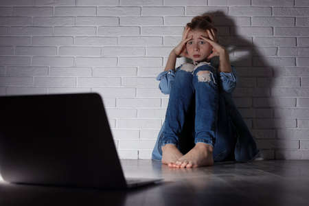 Scared teenage girl with laptop on floor in dark room. Danger of internet