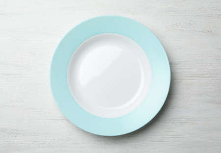 Stylish ceramic plate on white wooden background, top view
