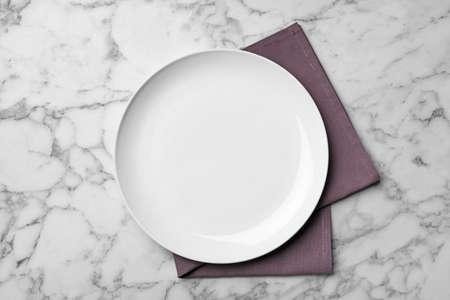 Stylish ceramic plate and napkin on marble background, flat lay