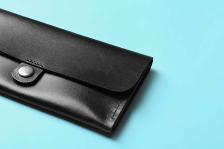 Leather wallet on color background, closeup with space for text. Stylish accessory
