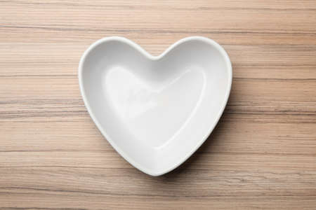 Heart shaped plate on wooden background, top view