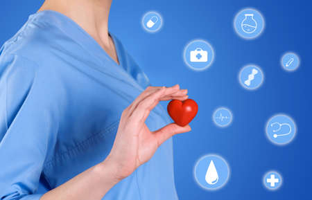Doctor with red heart and virtual icons on color background, closeup. Health insurance