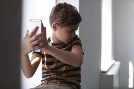 Frightened little child with smartphone indoors. Danger of internet