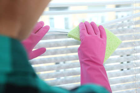 Woman wiping window blinds with rag indoors, closeup. Before and after cleaning