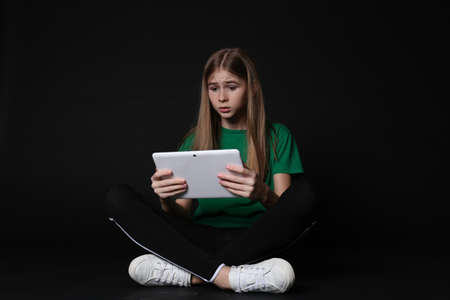 Shocked teenage girl with tablet on black background. Danger of internet