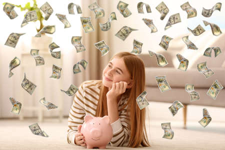 Teenager with piggy bank and flying money at home
