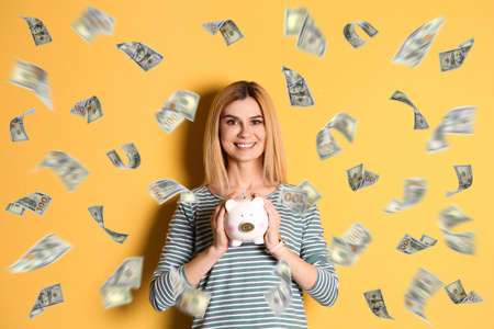 Happy woman with piggy bank and flying money on color background Imagens