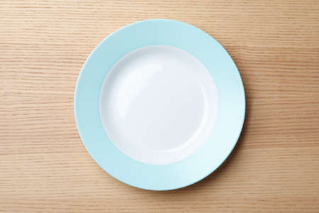 Stylish ceramic plate on wooden background, top view