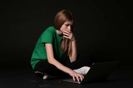Terrified teenage girl with laptop on black background. Danger of internet