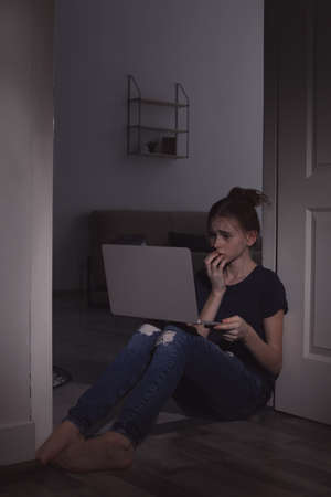 Frightened teenage girl with laptop on floor in dark room. Danger of internet