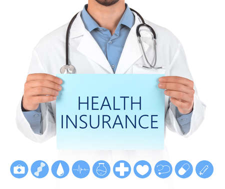 Doctor holding paper with text HEALTH INSURANCE on white background, closeup
