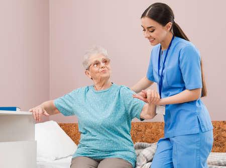 Nurse assisting senior woman on bed in hospital ward
