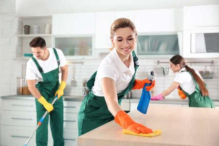 Mujer con un trapo y un rociador para limpiar la mesa con sus colegas en la cocina Foto de archivo