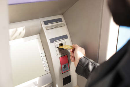 Man inserting credit card into cash machine outdoors, closeup