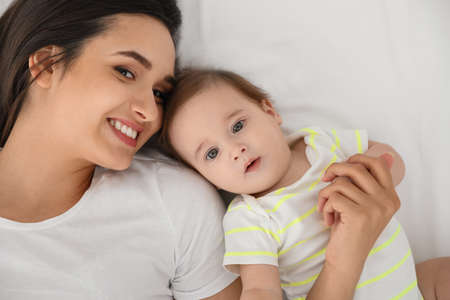 Portrait of mother with her cute baby lying on bed, top view Stock Photo - 124988393