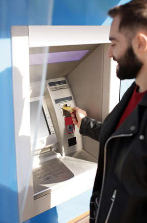 Young man inserting credit card into cash machine outdoors