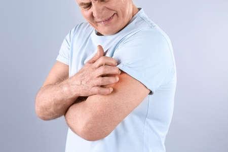 Senior man scratching arm on grey background, closeup. Allergy symptom