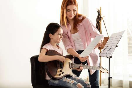 Kleines Mädchen, das mit ihrem Lehrer im Musikunterricht Gitarre spielt. Lernnotizen