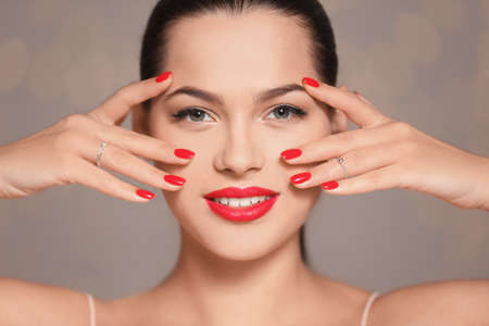 Beautiful young woman with bright manicure on blurred background, closeup. Nail polish trends