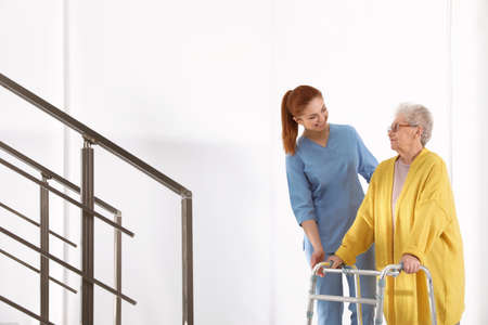 Nurse assisting senior woman with walker in hospital Stock Photo