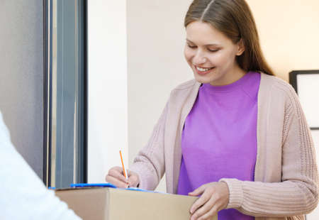 Woman receiving parcel from delivery service courier indoors