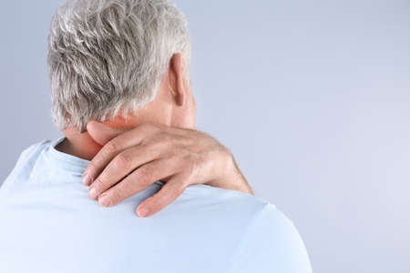 Senior man scratching neck on grey background, space for text. Allergy symptom
