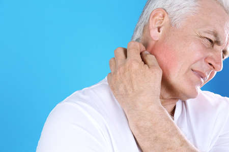 Senior man scratching neck on color background, closeup with space for text. Allergy symptom