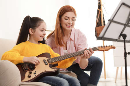 Little girl playing guitar with her teacher at music lesson. Learning notes