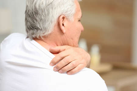 Senior man scratching shoulder indoors, closeup with space for text. Allergy symptom
