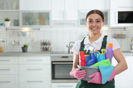 Retrato de mujer joven con lavabo de detergentes en la cocina. Servicio de limpieza