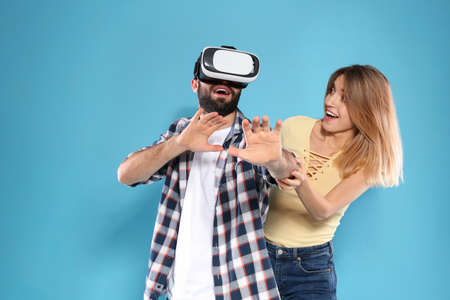 Young man playing video games with VR headset and emotional woman on color background Stock Photo
