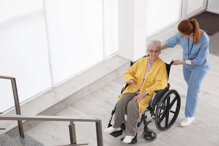 Nurse assisting senior woman in wheelchair at hospital