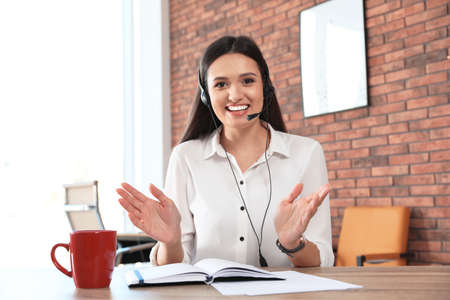 Young woman with headset looking at camera and using video chat in home office Banco de Imagens