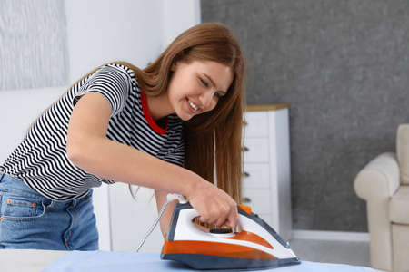 Young woman ironing clothes on board at home