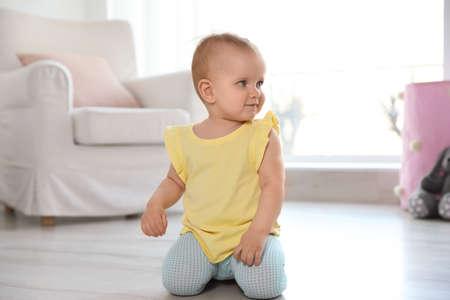 Cute baby girl on floor in room Archivio Fotografico - 124720360