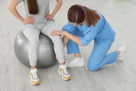 Professional physiotherapist working with female patient in rehabilitation center, closeup 写真素材