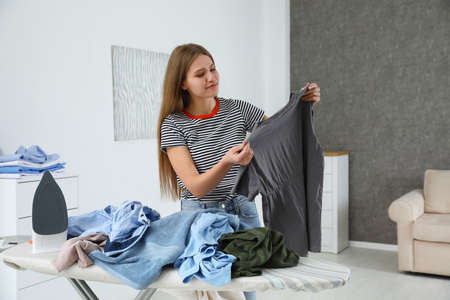 Young woman with clothes near ironing board at home Banco de Imagens - 124988450
