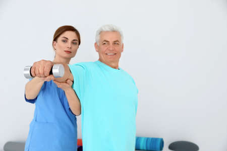 Professional physiotherapist working with senior patient in rehabilitation center. Space for text