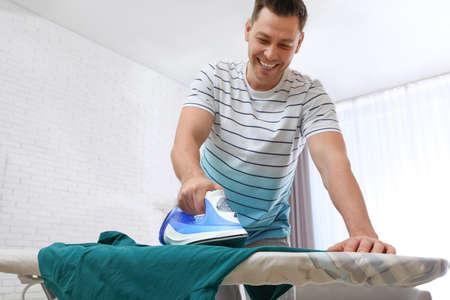 Hombre planchando ropa a bordo en casa